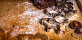 Sluit omhoog op peperkoekdeeg en vormen, snijders op de houten lijst stock afbeeldingen