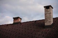 Sluit omhoog op twee die baksteenschoorsteen op dak in hemel wordt geïsoleerd Stock Fotografie