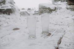 Sluit omhoog op twee lege bierglazen in de sneeuw Royalty-vrije Stock Afbeelding