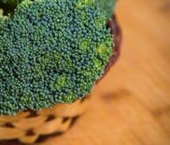 Sluit omhoog op Verse broccoli solated in mand op houten achtergrond Stock Afbeeldingen