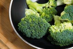 Sluit omhoog op Verse broccoli solated in pan op houten achtergrond Stock Afbeeldingen