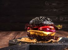 Sluit omhoog op zwarte hamburger die met geroosterde uien, tomatenplakken en sla wordt gevuld Stock Afbeelding