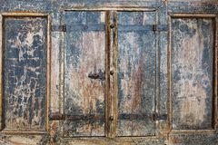 Sluit omhoog openluchtmening van een deel van oude gesloten houten blinden Detail van roestige metaalscharnieren vast met versche stock foto