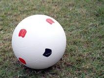 Sluit omhoog oude witte plastic voetbalbal op groen grasgebied royalty-vrije stock afbeeldingen