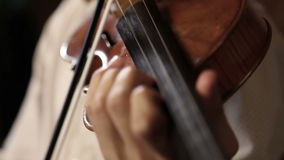 Sluit omhoog pan van een vioolspeler wordt geschoten in donkere ruimte die