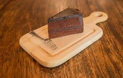 Sluit omhoog Plak van chocoladecake met frok op houten lijst Stock Foto
