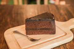 Sluit omhoog Plak van chocoladecake met frok op houten lijst Royalty-vrije Stock Foto's