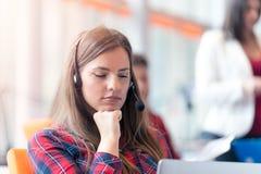 Sluit omhoog plan van een glimlachende onderneemster in een call centre stock foto