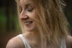 Sluit omhoog portret - de Mooie jonge bosnimf van de blondevrouw in witte kleding in altijdgroen hout royalty-vrije stock foto's