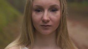 Sluit omhoog portret - de Mooie natuurlijke jonge bosnimf van de blondevrouw in witte kleding in altijdgroen hout - Kijkend stock footage