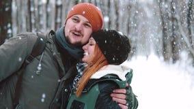 Sluit omhoog portret Paar gelukkig paar die, kussend, hebbend pret onder sneeuwval in langzame motie op de wintervakantie met de  stock footage