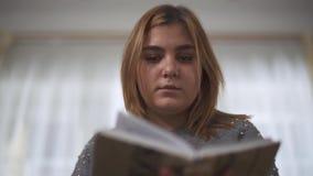 Sluit omhoog portret plus de zitting van het de lezingsboek van het groottemeisje bij bank in huis Het mollige boek van de vrouwe stock videobeelden