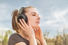Sluit omhoog portret van aantrekkelijke vrouw die van muziek op headphon genieten Royalty-vrije Stock Foto's