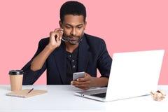 Sluit omhoog portret van Afrikaanse Amerikaanse zakenman gecontroleerde e-mail op zijn smartphone, zit voor laptop, die heeft onl stock foto's