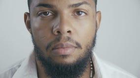Sluit omhoog portret van Afrikaanse Amerikaanse zakenman in wit overhemd bij witte achtergrond stock video