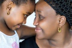 Sluit omhoog portret van Afrikaanse moeder en kind toetredende hoofden royalty-vrije stock afbeelding