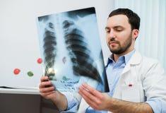Sluit omhoog portret van arts die borströntgenstraal bekijken in zijn bureau stock foto