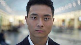 Sluit omhoog portret van Aziatisch mannetje die ernstig recht camera bekijken stock footage