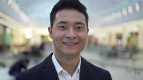 Sluit omhoog portret van Aziatisch mannetje met steunen het glimlachen rechtstreeks bekijkend camera stock videobeelden