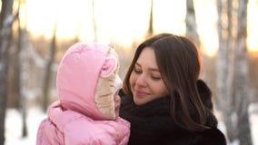 Sluit omhoog portret van baby en haar jonge, mooie moeder buiten bij sneeuwbomen op de achtergrond van het de winterpark Gelukkig stock foto's