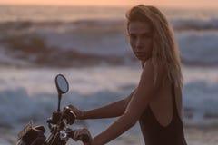Sluit omhoog portret van blond model in zwarte zwempakzitting op motorfiets, stock afbeelding