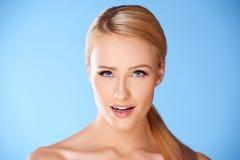 Sluit omhoog portret van blonde vrouw op blauw Royalty-vrije Stock Afbeeldingen