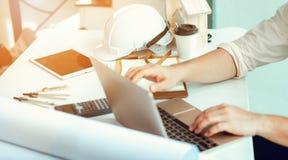Sluit omhoog portret van civiel-ingenieur gebruikend laptop aan de planning van PR royalty-vrije stock afbeelding