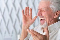 Sluit omhoog portret van de glimlachende hogere mens die thuis stellen royalty-vrije stock afbeeldingen