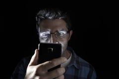 Sluit omhoog portret van de jonge mens die intensief wordt geïsoleerd aan het mobiele telefoonscherm kijken met blauwe ogen brede Stock Afbeeldingen