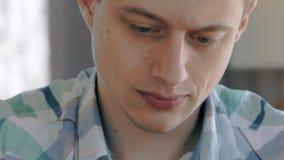 Sluit omhoog portret van de jonge mens die, langzame motie werken stock videobeelden