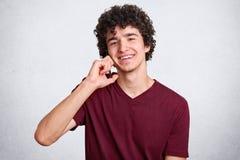 Sluit omhoog portret van de jonge mens met krullend haar, in kastanjebruine t-shirt die op telefoon spreken terwijl het bekijken  stock afbeelding