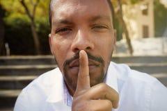 Sluit omhoog portret van de knappe vrolijke stille Amerikaanse Afrikaanse mens die stiltegebaar maken Royalty-vrije Stock Foto