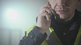Sluit omhoog portret van de man in de eenvormige bouwers en helm die door celtelefoon spreken voor de zwarte achtergrond stock videobeelden