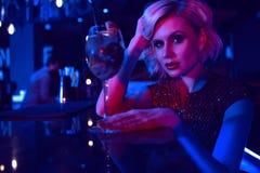 Sluit omhoog portret van de mooie zitting van de glam blonde vrouw bij de bar in de nachtclub in kleurrijke neonlichten drinkend  stock afbeeldingen