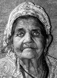 Sluit omhoog portret van de oude dakloze vrouw die van de Zigeunerbedelaar met gerimpelde gezichtshuid voor geld op de straat in  stock foto