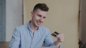Sluit omhoog portret van de vrolijke modieuze jonge mens terwijl hij online betaling gebruikend laptop en creditcard verricht Bli stock video
