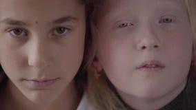 Sluit omhoog portret van donkerbruin meisje met bruine ogen en albinomeisje die met grijze ogen de camera bekijken Concept van stock footage