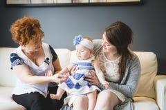 Sluit omhoog portret van drie generaties van vrouwen die dichte, grootmoeder, moeder en babydochter thuis zijn Stock Afbeelding