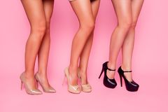 Sluit omhoog portret van drie mooie meisjes die hun naakte vlotte benen met één knie op roze achtergrond bogen tonen Royalty-vrije Stock Foto's