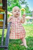Sluit omhoog Portret van een éénjarig 9 maandenkind in roze sundress Het meisje leert te lopen stock fotografie
