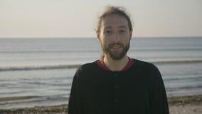 Sluit omhoog portret van een aantrekkelijke mens die op het strand op zonsopgang glimlachen - stock videobeelden