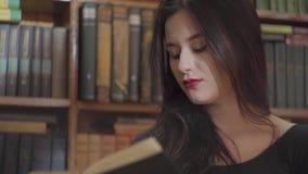 Sluit omhoog portret van een ernstige jonge student die met heldere make-up een boek in een bibliotheek lezen die bevinden zich v stock video