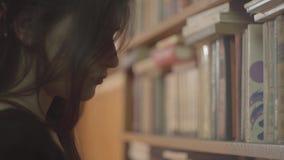 Sluit omhoog portret van een ernstige jonge student die met heldere make-up een boek in een bibliotheek lezen Het aantrekkelijke  stock videobeelden