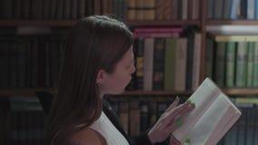 Sluit omhoog portret van een ernstige jonge vrouw die een boek in een bibliotheek lezen die zich voor boekenrek bevinden Vrije ti stock footage