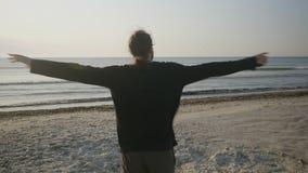 Sluit omhoog portret van een gelukkige jonge jongen met lang haar die pret op het strand hebben terwijl het uitdrukken van zijn v stock footage