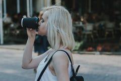Sluit omhoog portret van een glimlachend jong meisje met koffie Stock Afbeeldingen