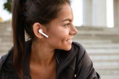 Sluit omhoog portret van een glimlachende geschiktheidsvrouw in oortelefoons Stock Afbeeldingen