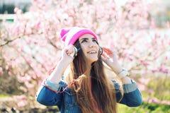 Sluit omhoog portret van een grappig jong swagmeisje die op weelderige tuin aan muziek in oortelefoons van slimme telefoonmp3 spe Stock Afbeeldingen