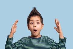Sluit omhoog portret van een grappige jongen die of met iets verrassen verrukken, die zijn handen omhoog op blauwe achtergrond in royalty-vrije stock afbeeldingen