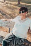 Sluit omhoog portret van een hogere vrouw in de parkzitting op een bank bij zonsondergang stock foto